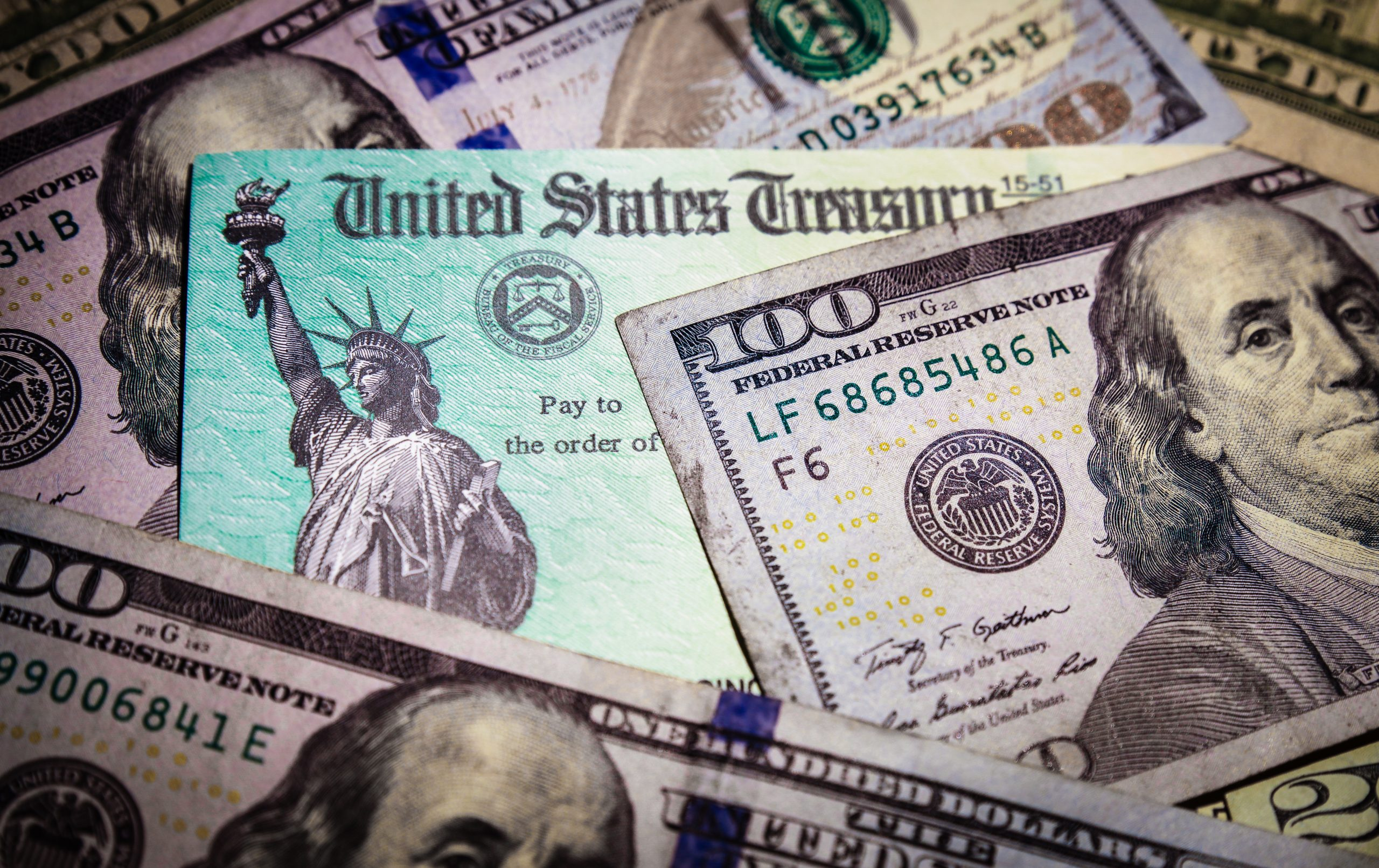 WASHINGTON DC - APRIL 2, 2020: United States Treasury check with US currency. Illustrates IRS tax refund or coronavirus economic relief package cash payments to taxpayers affected by the pandemic.
